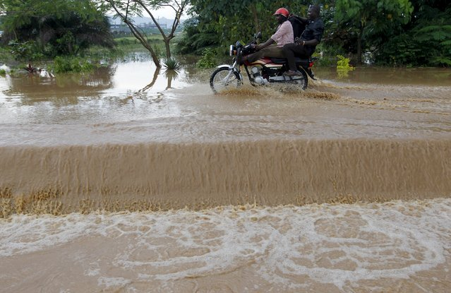 A motorcyclist with a pillion rides through flood waters on a street in Abuja, Nigeria, September 3, 2015. (Photo by Afolabi Sotunde/Reuters)