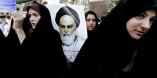 A protester holds a poster of the late revolutionary founder Ayatollah Khomeini during a demonstration against the film ridiculing Islam's Prophet Muhammad, in front of the Swiss Embassy in Tehran, which represents U.S. interests in Iran. (Photo by Vahid Salemi/Associated Press)