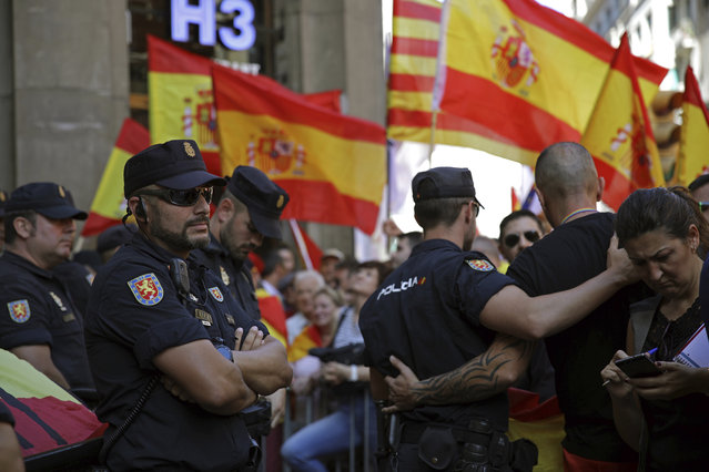 Spanish police officers watch as demonstrators march to protest the Catalan government's push for secession from the rest of Spain in downtown Barcelona, Spain, Sunday October 8, 2017. Sunday's rally comes a week after separatist leaders of the Catalan government held a referendum on secession that Spain's top court had suspended and the Spanish government said was illegal. (Photo by Emilio Morenatti/AP Photo)