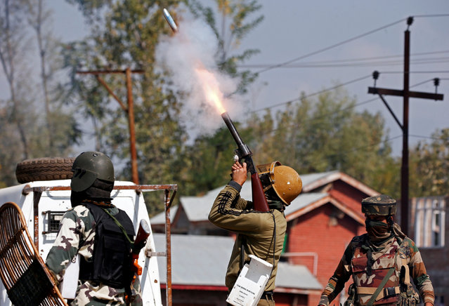 An Indian policeman fires a teargas shell towards the demonstrators during a protest before the funeral of of Nasrullah Mir, a suspected militant, who according to the local media was killed during a gun battle with Indian security forces at Hajin area of Bandipora district, October 11, 2017. (Photo by Danish Ismail/Reuters)