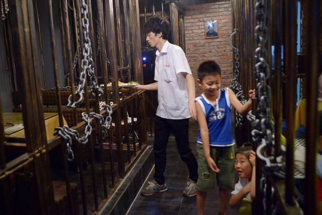 This picture taken on September 9, 2014 shows a waiter (L) handing over the food to customers (not in picture ) as two children play at a prison themed restaurant in Tianjin. (Photo by Wang Zhao/AFP Photo)