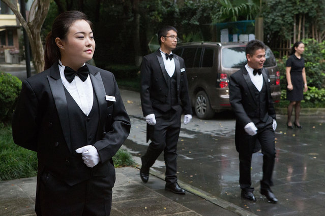 Students wait outside to greet guests and help them from their cars before a formal dinner at The International Butler Academy China on September 16, 2014 in Chengdu, China. (Photo by Taylor Weidman/Getty Images)