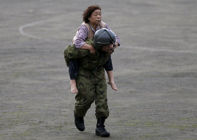 A woman is carried by a Japan Self-Defense Force (JSDF) member after being rescued by a helicopter from an area flooded by the Kinugawa river, caused by typhoon Etau, upon their arrival at Ishige Sports Park acting as a evacuation center in Joso, Ibaraki prefecture, Japan, September 10, 2015. (Photo by Issei Kato/Reuters)