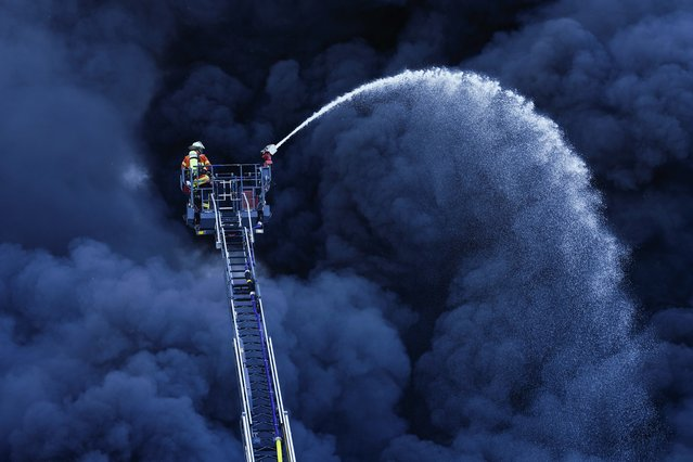 Firefighters are fighting a fire at a plastics factory in front of a huge cloud of smoke in Ladenburg, Germany, Tuesday, May 19, 2020. (Photo by Uwe Anspach/dpa via AP Photo)