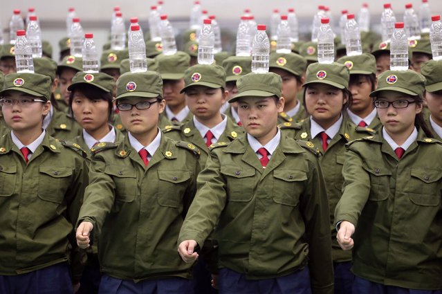 Students in military uniforms balance bottles of water on their heads as they practice goose-stepping marching during a military training session at a college in Zhengzhou, Henan province September 17, 2014. (Photo by Reuters/Stringer)
