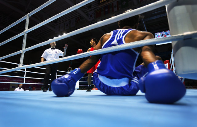 Bhutan's Sigyel Phub (C) reacts after Pakistan's Nadir fell during their Men's Bantam Weight preliminary boxing bout at Seonhak Gymnasium during the 17th Asian Games in Incheon September 24, 2014. (Photo by Tim Wimborne/Reuters)