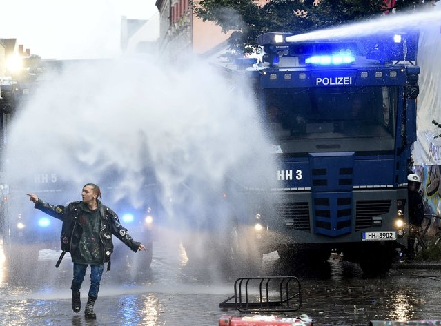 A left-wing protestor walks in front of police water cannons during a demonstration against a Nazi demonstration, which was forbidden by authorities, in Hamburg's Schulterblatt street in Schanzenviertel district, September 12, 2015. More than 10000 people demonstrate against the planned Nazi rally. (Photo by Fabian Bimmer/Reuters)