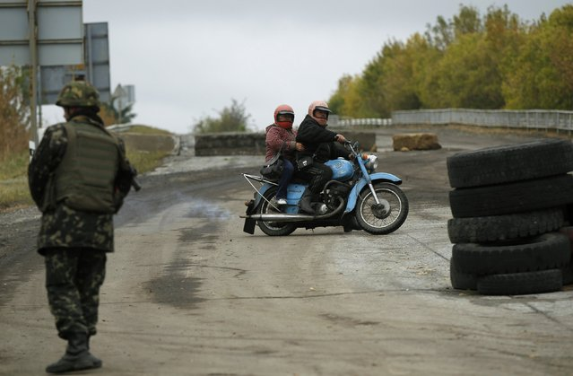 Local residents drive at the checkpoint near the eastern Ukrainian town of Debaltseve, September 25, 2014. (Photo by David Mdzinarishvili/Reuters)