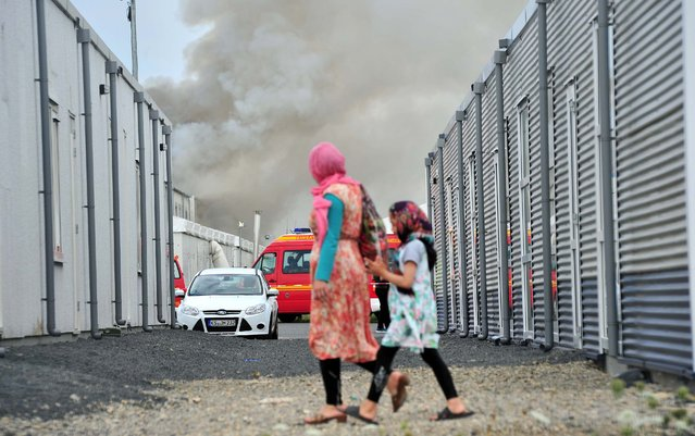Refugees walk past  containers as smoke billows in background in the refugee camp near Kassel,  Germany,  Sunday, August 14, 2016. German authorities say 16 asylum seekers suffered from smoke inhalation after a fire broke out at a container housing facility in the central city of Kassel. The Kassel fire department told the dpa news agency the fire started inside one of the residences Sunday and that an anti-migrant attack had been ruled out. (Photo by Bernd Schoelzchen/DPA via AP Photo)