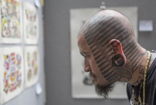 A man browses tattoo designs during the 10th International Tattoo Convention in London September 27, 2014. (Photo by Neil Hall/Reuters)