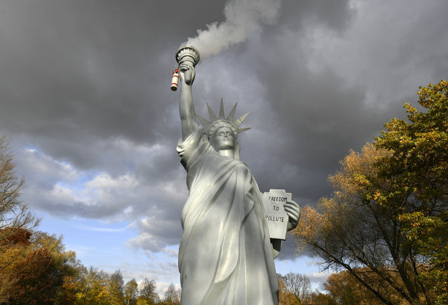 A replica of the Statue of Liberty by Danish artist Jens Galschiot emits smoke in a park outside the 23rd UN Conference of the Parties (COP) climate talks in Bonn, Germany, Friday, November 17, 2017. (Photo by Martin Meissner/AP Photo)