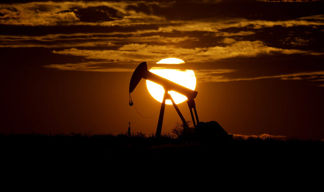 The sun sets behind an idle pump jack near Karnes City, Texas, Wednesday, April 8, 2020. Demand for oil continues to fall due to the new coronavirus outbreak. (Photo by Eric Gay/AP Photo)