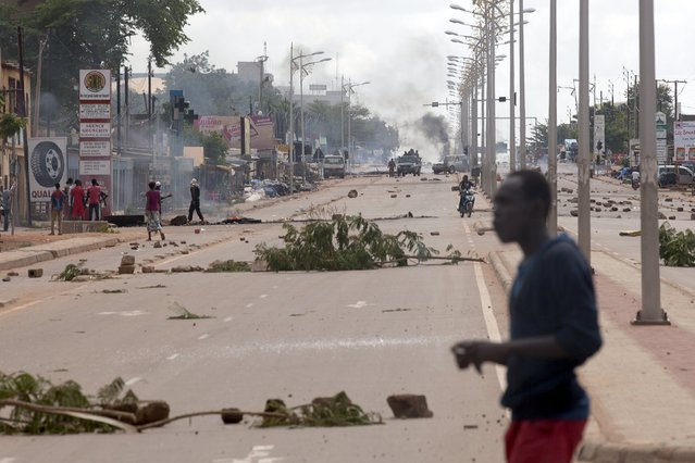 Members of the presidential guard dismantle roadblocks set up by anti-coup protesters in Ouagadougou, Burkina Faso, September 18, 2015. (Photo by Joe Penney/Reuters)