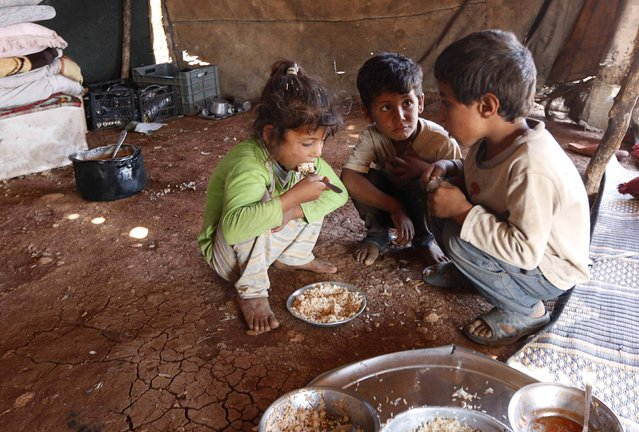 Internally displaced children, who along with their family fled the violence in Aleppo's Handarat area, eat inside a tent in the northern countryside of Aleppo October 8, 2014. (Photo by Jalal Al-Mamo/Reuters)