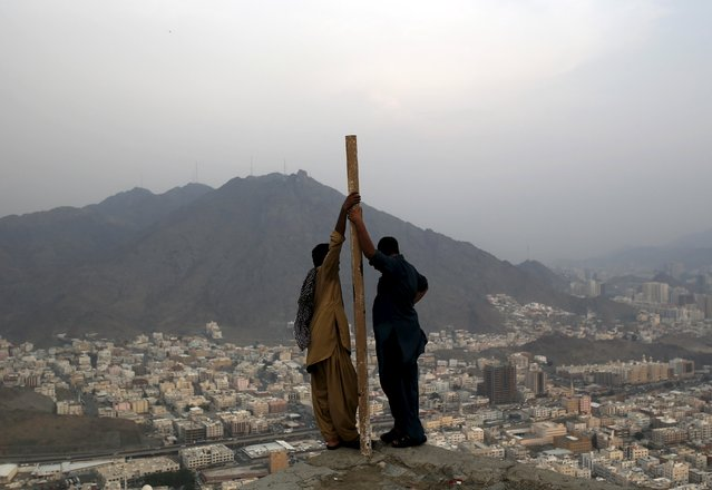 Muslim pilgrims look at the city landscape after visiting Hera cave, where Muslims believe Prophet Mohammad received the first words of the Koran through Gabriel, at the top of Mount Al-Noor during the annual haj pilgrimage in the holy city of Mecca, September 21, 2015. (Photo by Ahmad Masood/Reuters)