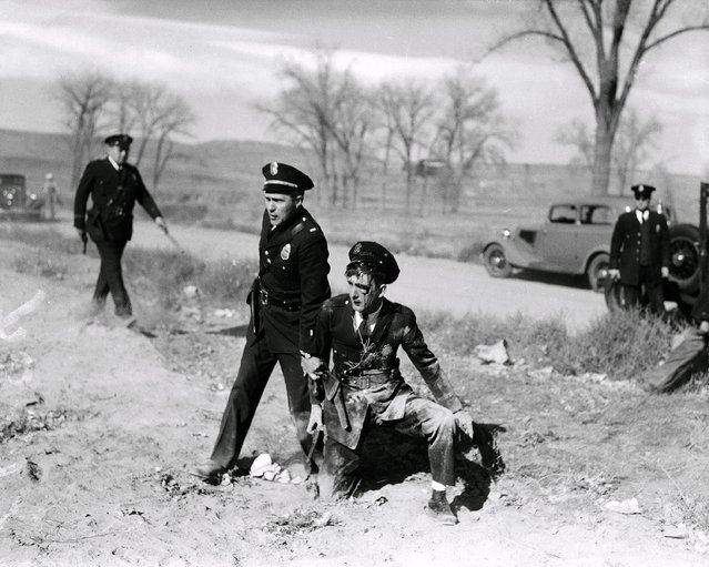 A fellow officer comes to the aid of injured patrolman C.V. Satt, who was pelted with rocks and beer bottles during a clash between police and relief demonstrators in Denver September 23, 1935. (Photo by Henry G. Eisenhand/AP Photo)