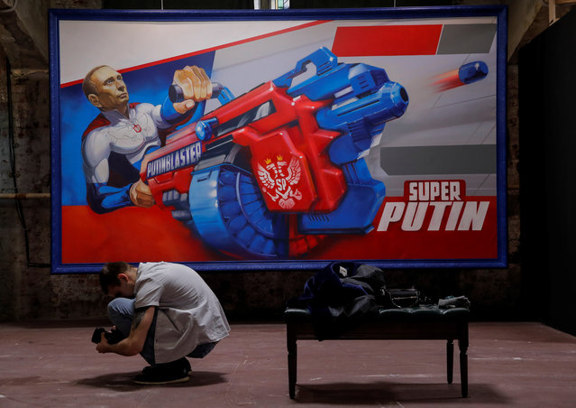 """A photographer takes pictures in front of a painting depicting Russian president Vladimir Putin at the """"SUPERPUTIN"""" exhibition at UMAM museum in Moscow, Russia on December 6, 2017. (Photo by Maxim Shemetov/Reuters)"""