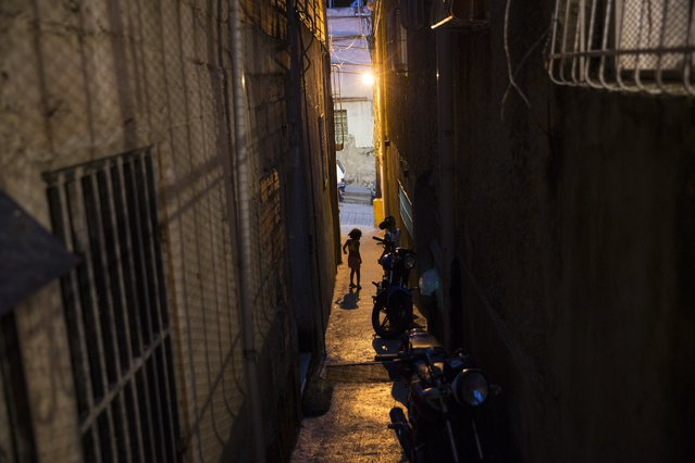 A girl plays amid the corridor between two building in a popular neighborhood in Caracas, Venezuela, Friday, October 20, 2017. (Photo by Rodrigo Abd/AP Photo)