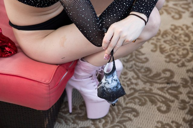 """A dancer holds a mask due to COVID-19 at Cheerleaders Gentlemen's Club, which received a Paycheck Protection Program (PPP) loan from the Small Business Administration, in Gloucester City, New Jersey, U.S. July 17, 2020. But nearly four months since the launch of the loan initiative known as the Paycheck Protection Program (PPP), it is still unclear whether the SBA can make it rain for them. The Trump administration has barred companies that """"present live performances of a prurient sexual nature"""" from participating. Clubs sued, and two federal judges rebuked the SBA for excluding the establishments from receiving the forgivable loans meant to protect jobs amid the health crisis. (Photo by Rachel Wisniewski/Reuters)"""
