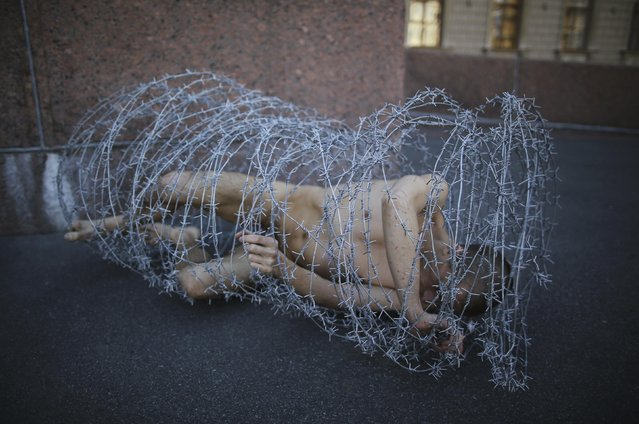 Artist Pyotr Pavlensky lies on the ground, wrapped in barbed wire roll, during a protest action in St. Petersburg May 3, 2013. (Photo by Artur Bainozarov/Reuters)
