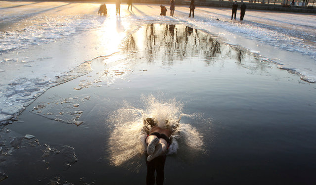 A winter swimmer dives into the icy waters of a river at a park in Shenyang, Liaoning province, China December 18, 2017. (Photo by Reuters/China Stringer Network)