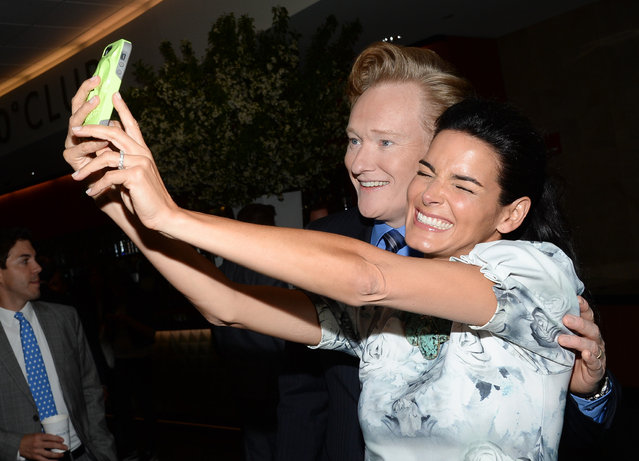 Conan O'Brien and Angie Harmon, right, take a selfie backstage at the TNT and TBS Network 2014 Upfront Presentations at Madison Square Garden on Wednesday, May 14, 2014, in New York. (Photo by Evan Agostini/Invision/AP Photo)
