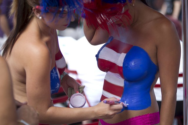Women who pose for tips wearing body paint and underwear help each other get ready in Times Square in New York in this August 19, 2015 file photo. New York City will try and impose order on the chaos of Times Square with new rules to control the costumed characters and women clad in little more than body paint who have drawn criticism for aggressive behavior in seeking tips from tourists. (Photo by Carlo Allegri/Reuters)