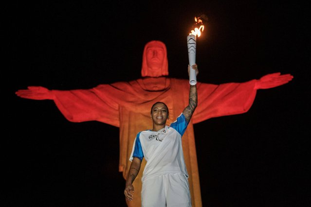 Brazilian judoka Rafaela Silva, who won the gold medal during the Rio 2016 Olympic Games, holds up the torch for the Rio 2016 Paralympic Games in front of the statue of Christ the Redeemer atop Mount Corcovado in Rio de Janeiro on September 6, 2016. (Photo by Yasuyoshi Chiba/AFP Photo)