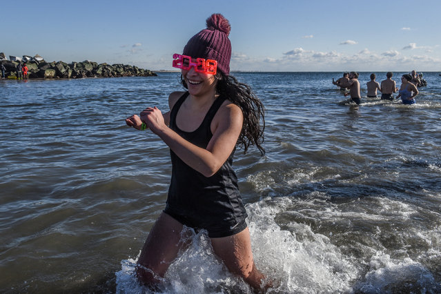 Swimmers run into the water of the Atlantic Ocean on Coney Island Beach in Brooklyn, New York City on January 1, 2018. (Photo by Stephanie Keith/Reuters)