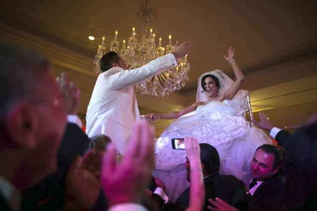 Megan Moshar, 26, who is of Persian, German and Filipino descent, dances with her husband George Safar, 27, whose parents are from Syria, as they are both lifted into the air during their wedding reception in Pasadena, California August 16, 2014. (Photo by Lucy Nicholson/Reuters)