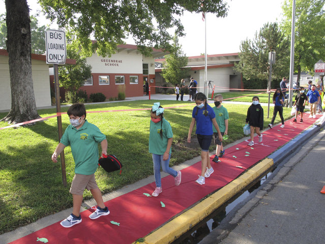 Students return to Greenbrae Elementary School in Sparks, Nev., on Tuesday, August 18, 2020, for the first time since March with mandatory masks and social distancing to help guard against the spread of the coronavirus. Washoe County schools are using a combination of classroom instruction and distance learning. Nevada's largest school district resumes school in Las Vegas next week using strictly remote learning. (Photo by Scott Sonner/AP Photo)