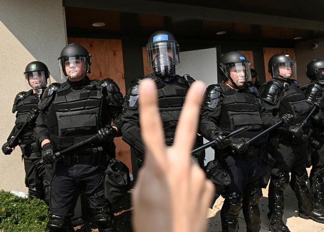 Adam Andrew Salgado holds up a peace sign as police hold a perimeter, during protests following the police shooting of Black man Jacob Blake, outside the Kenosha County Public Safety Building in Kenosha, Wisconsin, U.S. August 24, 2020. (Photo by Stephen Maturen/Reuters)