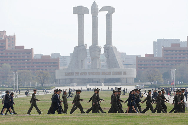 Soldiers walk in front of the Monument to the Foundation of the Workers' Party in Pyongyang, North Korea on April 16, 2017. (Photo by Damir Sagolj/Reuters)