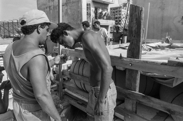 Men take a break while getting ready to lower their makeshift boat from a rooftop onto a truck and launch it into the Straits of Florida towards the U.S., on the last day of the 1994 Cuban exodus in Havana, in this September 13, 1994 file photo. (Photo by Rolando Pujol Rodriguez/Reuters)