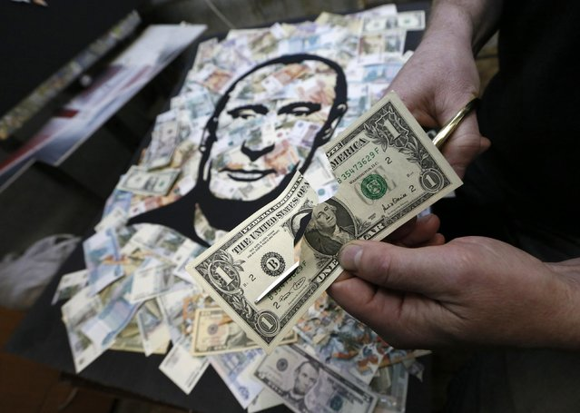 Russian artist Vasily Slonov cuts a U.S. one dollar banknote as he creates an artwork depicting a portrait of Russian President Vladimir Putin based on a layer of U.S. dollars, Russian and Soviet roubles at his workshop in Krasnoyarsk, Siberia, November 13, 2014. (Photo by Ilya Naymushin/Reuters)