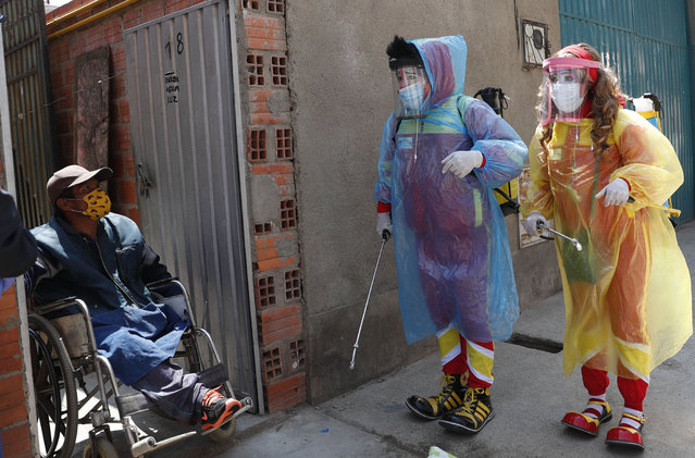 Clowns Perlita and Tapetito, wearing protective gear amid the new coronavirus pandemic, speak with resident Enrique Zeballos as they arrive to disinfect his home free of charge, in El Alto, Bolivia, Friday, September 11, 2020. The lack of traditional employment for the clowns due to the pandemic has led them towards other avenues of making money. But for people with limited income they provide their disinfection services free of charge. (Photo by Juan Karita/AP Photo)