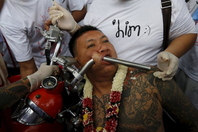 A devotee of the Chinese Bang Neow shrine pierces a motorcycle handlebar through his cheeks before a procession celebrating the annual vegetarian festival in Phuket, Thailand October 18, 2015. (Photo by Jorge Silva/Reuters)