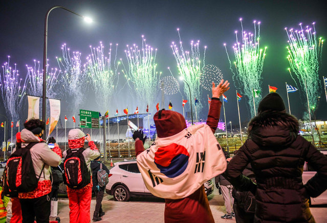 People with a South Korean flag waves as fireworks get off outside the stadium during the opening ceremony of the Pyeongchang 2018 Winter Olympic Games at the Pyeongchang Stadium on February 9, 2018. (Photo by Martin Bernetti/AFP Photo)