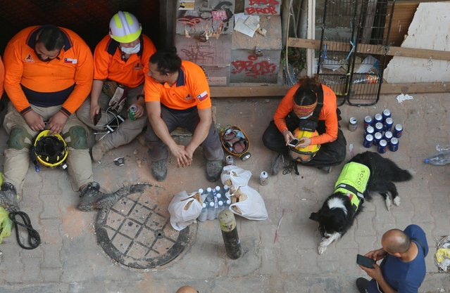 The Chilean rescue team sits together, with their dog Flash, as they take a break from checking buildings that collapsed from last month's port blast in Gemmayze, Beirut, Lebanon on September 4, 2020. (Photo by Aziz Taher/Reuters)