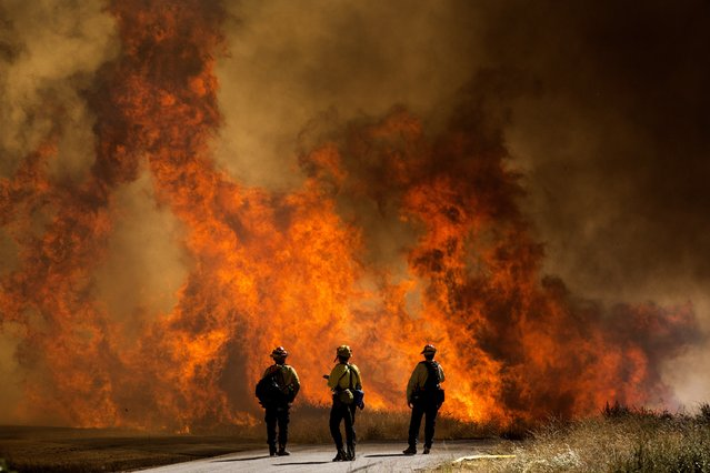 Firefighters watch as flames flare at the Apple Fire in Cherry Valley, Calif., Saturday, August 1, 2020. A wildfire northwest of Palm Springs flared up Saturday afternoon, prompting authorities to issue new evacuation orders as firefighters fought the blaze in triple-degree heat. (Photo by Ringo H.W. Chiu/AP Photo)
