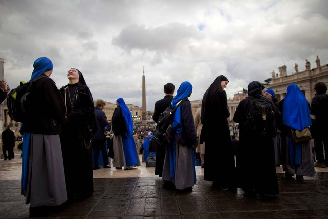Nuns gather after a Mass for the election of a new pope outside St. Peter's Basilica, at the Vatican, March 12, 2013. (Photo by Oded Balilty/Associated Press)