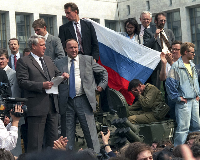 In this August 19, 1991 file photo, Russian President Boris Yeltsin, foreground left, addresses the crowd standing atop of a tank in front of the Russian Government building, also known as White House, surrounded by his bodyguards, Alexander Korzhakov, center, and Viktor Zolotov, top center, in Moscow, Russia. As the 25th anniversary of the so-called August Coup draws near this Friday, The Associated Press has talked to participants and witnesses of those critical days when Muscovites turned out to defend the spirit of democracy that Gorbachev had unleashed, and many Soviet officers defied their orders and sided with the people, ensuring that that the plotters failed. (Photo by AP Photo)