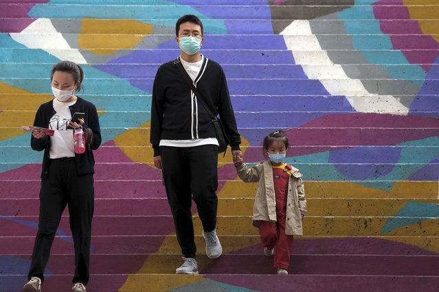 A family wearing face masks to help curb the spread of the coronavirus walk down a colourful staircase at a shopping mall in Beijing, Sunday, October 11, 2020. Even though the spread of COVID-19 has been all but eradicated in China, the pandemic is still surging across the globe with ever rising death toll. (Photo by Andy Wong/AP Photo)