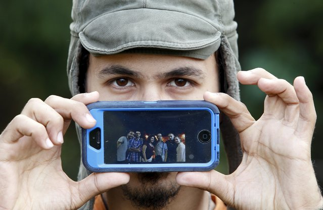 Migrant Muhammad from Damascus, Syria, shows a picture of his best friends as he waits to cross the Slovenia-Austria border in Sentilj, Slovenia October 25, 2015. (Photo by Srdjan Zivulovic/Reuters)