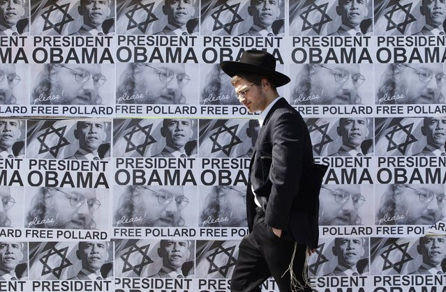 An ultra-Orthodox Jewish man walks past posters calling for U.S. President Barack Obama to free Jonathan Pollard from a U.S. prison, in Jerusalem March 20, 2013. Obama arrives in Israel on Wednesday without any new peace initiative to offer disillusioned Palestinians and facing deep Israeli doubts over his pledge to prevent a nuclear-armed Iran. Pollard, a former U.S. Navy intelligence analyst, has been serving a life sentence in the United States since he was caught spying for Israel in the 1980s. (Photo by Baz Ratner/Reuters)