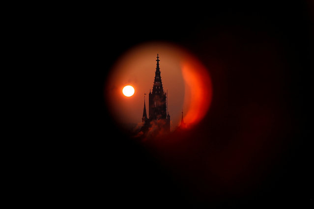 The sun rises behind the Muenster Cathedral during a cold morning in Bern, Switzerland February 28, 2018. Picture taken through a metal pipe. (Photo by Stefan Wermuth/Reuters)