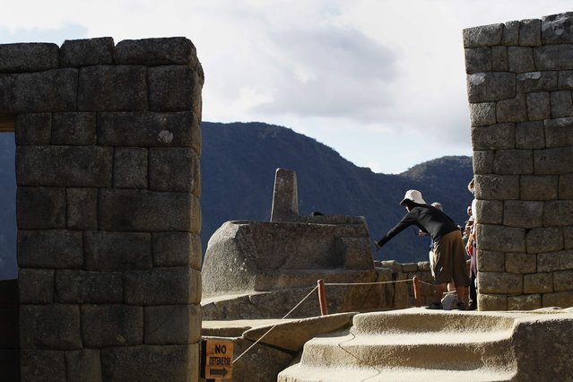 "A visitor touches the Intihuatana solar clock, believed to generate ""good energy"", at the Inca citadel of Machu Picchu in Cusco December 2, 2014. (Photo by Enrique Castro-Mendivil/Reuters)"