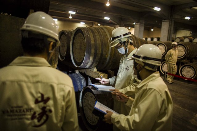 Workers check on casks in Suntory Holdings' Yamazaki Distillery in Shimamoto town, Osaka prefecture, near Kyoto, December 1, 2014. (Photo by Thomas Peter/Reuters)