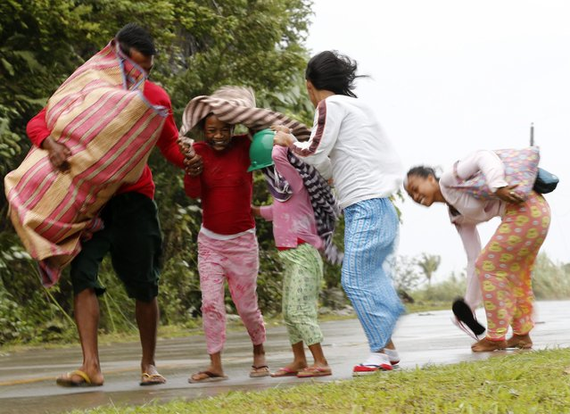 Filipino residents evacuate to safer ground in the town of Marabot, Samar island, Philippines, 06 December 2014. Typhoon Hagupit is speeding up and expected to make landfall in the eastern Philippines later 06 December, a senior weather official said. (Photo by Francis R. Malasig/EPA)