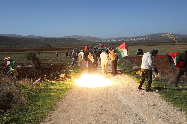 A picture shows light from a stunt grenade fired by Israeli forces to disperse Palestinian protesters during a demonstration intended to plant 300 olive trees in the village of Turmus Aya near Ramallah, in the Israeli-occupied West Bank, on December 10, 2014. Ziad Abu Ein, who was in charge of the issue of Israeli settlements for the Palestinian Authority, died after scuffles with Israeli forces during the protest march in the West Bank, medical and security sources told AFP. (Photo by Abbas Momani/AFP Photo)